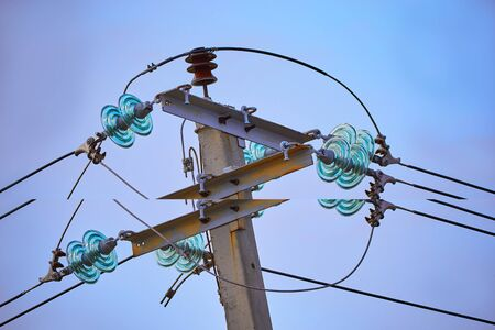 The top of electric pole on blue sky background