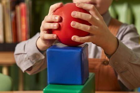 A red ball and a blue cube in the hands of a child