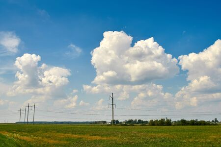 Huge white clouds in the sky over green fields, trees, forests. Electric poles
