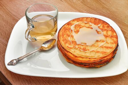 Waffle cake with a spoon lying smeared with condensed milk, a Cup of green tea 版權商用圖片