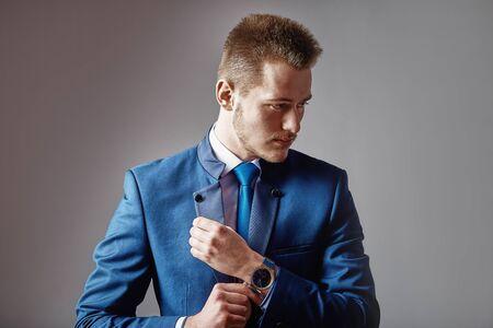 A man dressed in a suit over dark grey background. 版權商用圖片