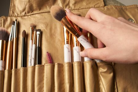 Cosmetic Makeup Brush in female hand on recruitment background.