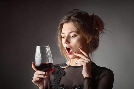 Beautiful young woman with glass of wine on gray background