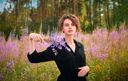 A young girl stands iin a blooming field of Ivan-tea with a bouquet of flowers.