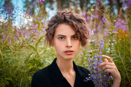 Portrait of a young beautiful girl with a bouquet of flowers on the background of a blooming field of Ivan-tea.