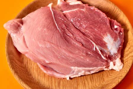 A plate of raw pork meat on an orange background 版權商用圖片
