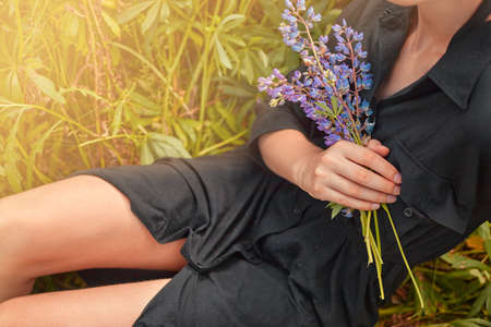 A bouquet of lupine in the hand of a girl sitting on the grass 版權商用圖片