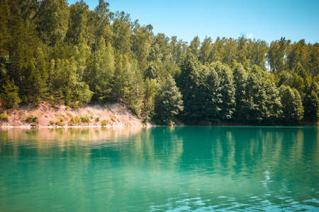 Forest lake with an emerald color of water. 版權商用圖片