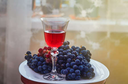 A glass of red wine on the background of grape.