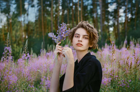 Young young girl with a bouquet of lupines in her hand against the background of blooming Ivan-tea
