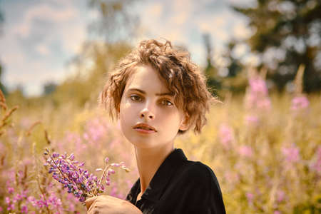 A beautiful young girl with a bouquet of lupine in her hand