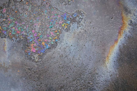 Gas stain on wet asphalt caused by a leak under a car or truck, abstract background Stock Photo