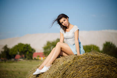 A young woman is sitting on a round bale of straw Imagens