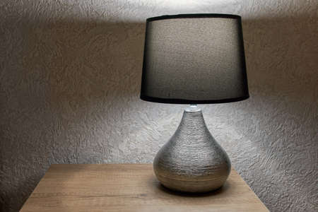 tylish lamp on table against wall, space for text.