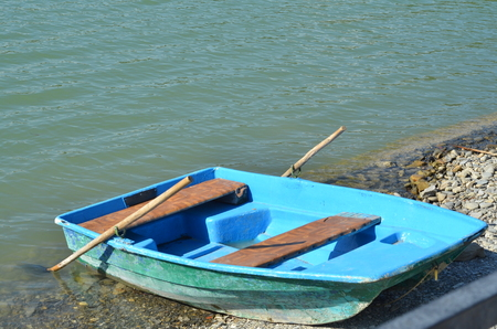 alpine zone: Old wooden boat for water walks on the pebbled shore of a mountain lake