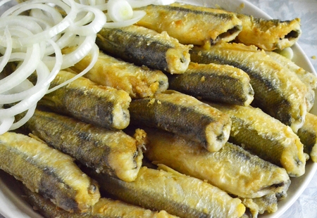 smelt: Fried fish smelt lies on a dish with chopped onions Stock Photo
