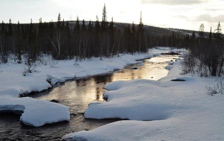 Kola Peninsula, Russia: Freezing winter northern mountain river Kurka. Evening, sunset, dusk Stock Photo