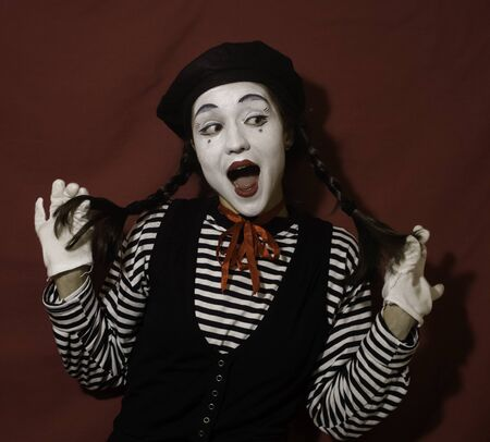 Beautiful mime girl smiles and holds her pigtails with her hands. 写真素材