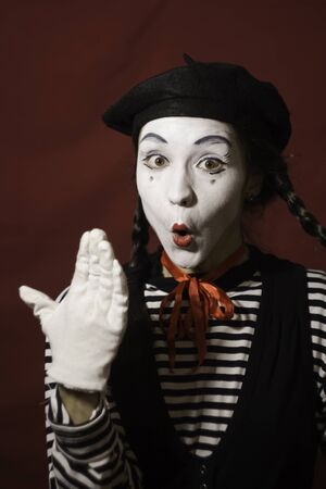 Beautiful mime girl grimaces and holds her pigtails with her hands.