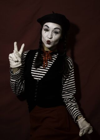 Beautiful mime girl grimaces and shows a victory sign with her hand.