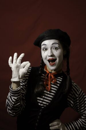 Beautiful mime girl smiling, showing ok sign.