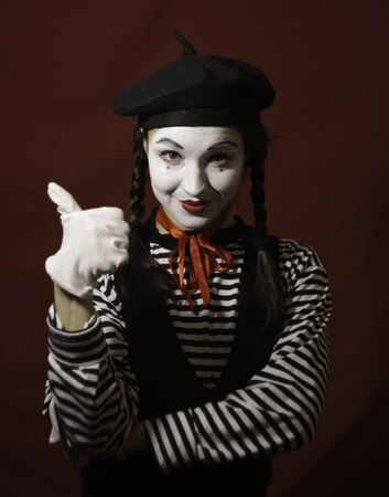 Beautiful girl mime smiles, shows thumb up. 写真素材