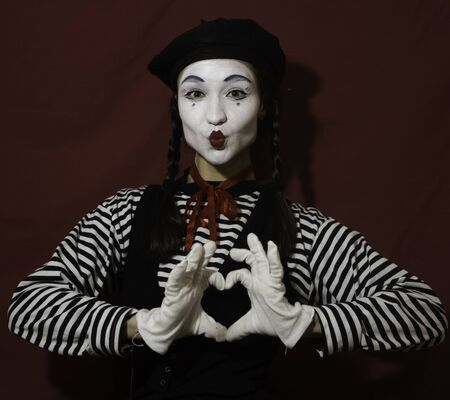 Beautiful girl mime smiles and makes a gesture of a beating heart with her hands looking at the camera. Beautiful girl in the image of a mime folds a heart from her hands looking at the camera.