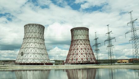 View of the power plant and cooling towers. The smoke goes out from a cooling tower of an operating power station. Cooling towers of a thermoelectric power station are reflected in a technical reservoir. Concept of ecology, environmental protection. Banco de Imagens