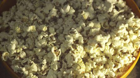 Fresh crispy popcorn lies in a bucket. Fresh hot popcorn lies in an orange bowl. Cinema pop corn background.
