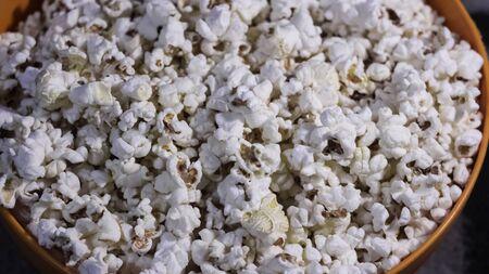 Fresh hot popcorn lies in an orange bowl.Fresh crispy popcorn lies in a bucket. Cinema pop corn background.