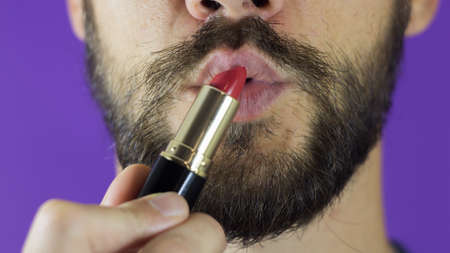 A young guy with a beard looks at the red lipstick and smiles.Close-up of a bearded man. He examines a bright red lipstick.A bearded man takes out lipstick, looks at her and smiles. Фото со стока