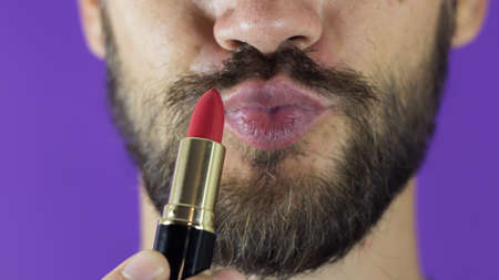 A young guy with a beard paints his lips with red lipstick. Close-up of a bearded man, he painted lips with bright lipstick. A bearded man puts red lipstick on his lips, smiles and smacks his lips. Фото со стока
