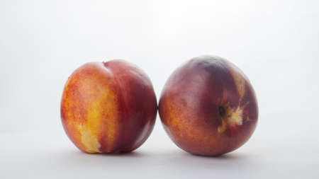 Fresh juicy peaches on a white plate. Close-up Fresh organic peaches nectarine on a white plate.