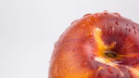 A drop of water flows down a fresh juicy peach. Fresh organic Peach covered with dew drops. Fresh juicy peaches on a white plate.