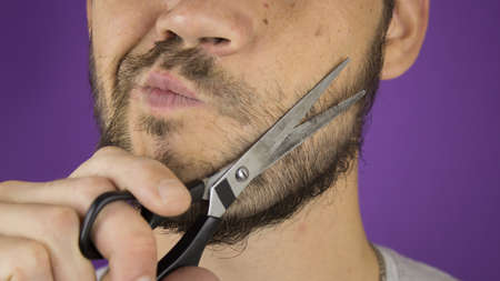 Handsome young guy trims his beard with scissors. 免版税图像