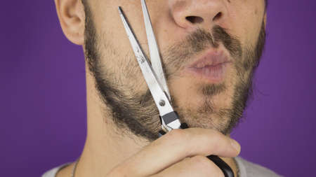 Handsome young guy trims his beard with scissors. Фото со стока