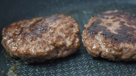 A chef puts beef patties on the grill. A juicy beef cutlet, fried in a pan. Close-up of beef cutlet for a burger on the grill.