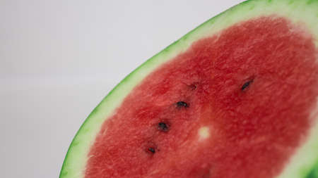 A slice of ripe watermelon rotates on a plate. Close up of watermelon pulp with seeds inside. Фото со стока