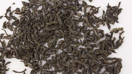 A handful of large leaf black tea on a white plate. Close-up of large leaf black tea on a white background. Dried black tea leaves on a plate.