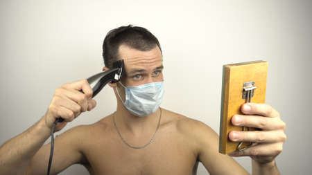 A young guy in a medical protective mask shaves his hair using a hair clipper while sitting at home in quarantine. A young handsome guy in a protective mask cuts his own hair with an electric trimmer during a pandemic.