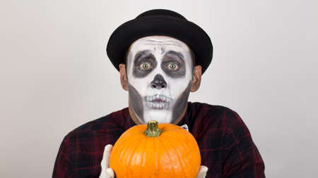 A horrible man in clown make-up holds a pumpkin, symbol of Halloween. A scary clown looks at the camera, holds a pumpkin in his hands and threatens her with a knife. Halloween costume. Banque d'images