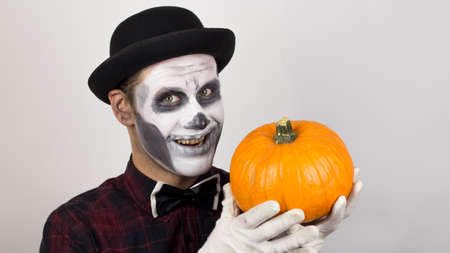 A horrible man in clown make-up holds a pumpkin, symbol of Halloween. A scary clown looks at the camera, holds a pumpkin in his hands and threatens her with a knife. Halloween costume. Zdjęcie Seryjne