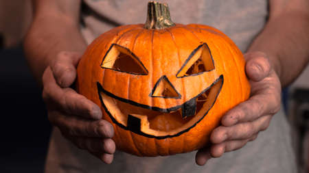 A young man, holds out a halloween pumpkin or jack-o-lantern . The young master made a jack-o-lantern for the Halloween party.