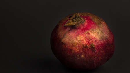 Ripe juicy pomegranate lies on gray