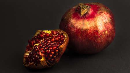 Ripe juicy pomegranate lies on a gray background. Ripe organic pomegranate fruits lie on a gray background. Healthy food concept. Banco de Imagens