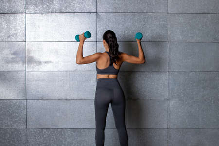 Female fitness trainer with dumbbells in her hand showing her back in front of a metal background with athletic shape