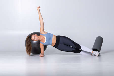 Perfect side plank. Full length of young beautiful woman in sportswear doing side plank with one arm up and looking at camera in front of white background with fitness equipment