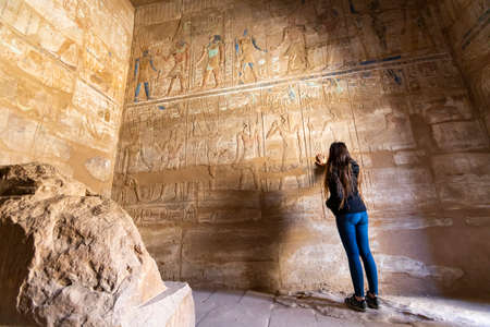 young woman touching egyptian hieroglyphic wall Banco de Imagens