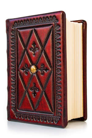 Small red leather book with deep embossed frame and yellowed pages standing isolated to the table Archivio Fotografico