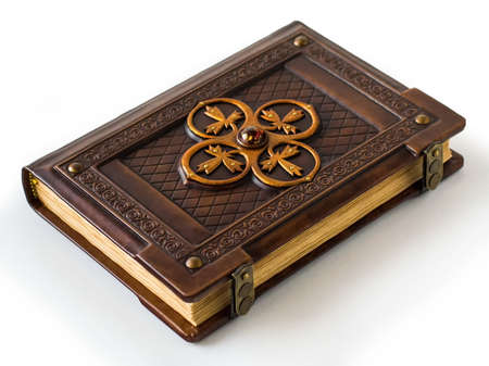 Vintage leather bound book with large brass ornament and amber stone in the center of the book. Laying on the table with view from the right side.